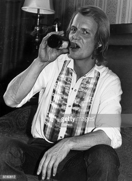 American actor and pop singer David Soul takes a drink from a bottle of lager beer while sitting on a sofa shortly before the start of his 13city...
