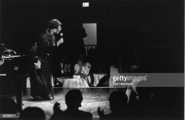 Fulllength image of American jazz vocalist Ella Fitzgerald leaning forward while singing into a microphone on stage in front of an audience in the...