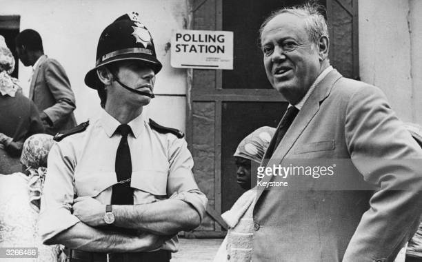Governer of Rhodesia Lord Soames with a British policeman on guard outside a polling booth in Salisbury during the Black vote in the Rhodesian...