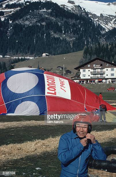 Soichiro Honda founder of the Honda motor company fastening his helmet while waiting for his hot air balloon to inflate in Gstaad Switzerland