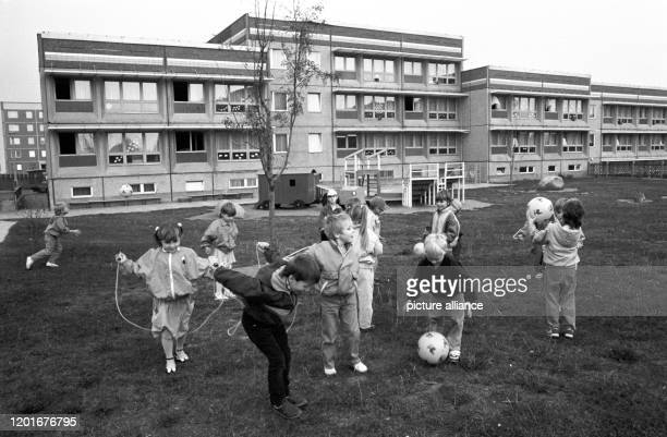 March 1989, Saxony, Torgau: Children play in front of the typical GDR-new-build kindergarten - often a combination of day care centre and crèche - of...