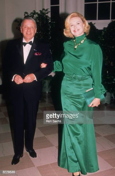 Full-length image of American actor and singer Frank Sinatra posing with his fourth wife, Barbara Marx, outdoors at a White House State Dinner for...