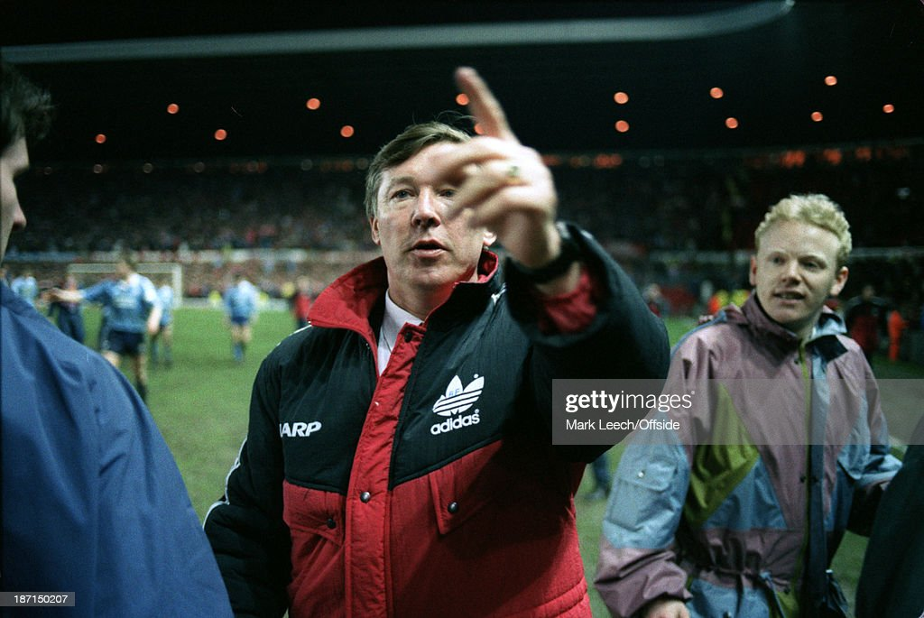 11 March 1992 Football League Cup - Manchester United v Middlesbrough - United manager Alex Ferguson is surrounded by celebrating fans as they invade the pitch after the match.
