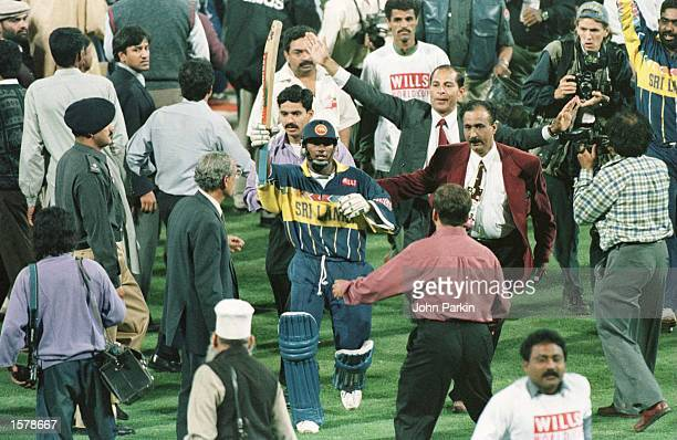 Aravinda De Silva raises his bat as he comes off the field after leading Sri Lanka to victory in the Cricket World Cup Final between Australia and...