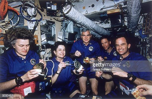 NASA's STS74 Atlantis Space Shuttle crew enjoying a meal aboard Russia's MIR Space Station Their mission is part of the first phase of the...
