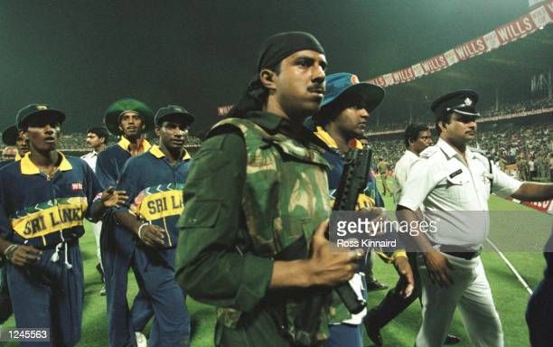 Riot police lead the Sri Lankan team off the pitch after the abandonment of the semifinal in the Cricket World Cup between India and Sri Lanka played...