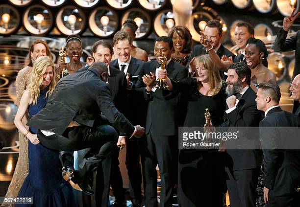 HOLLYWOOD CA March 2 2014 BEST Picture 12 YEARS A SLAVE director Steve McQueen leaps into the air as he celebrates with his cast on stage during the...