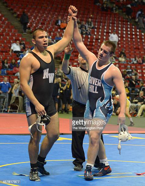 Showing good sportsmanship Logan Kirby of River Hill raises the hand of Luis Beteta of Northwest after winning the 220 pound championship on March 2...