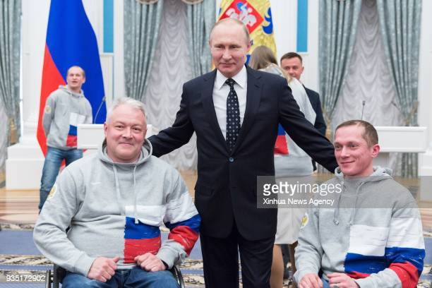 MOSCOW March 20 2018 Russian President Vladimir Putin poses with medalists of the Pyeongchang 2018 Winter Paralympics during an awarding ceremony in...