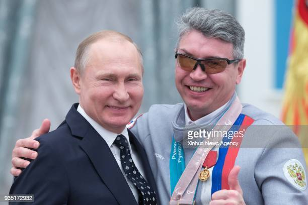 MOSCOW March 20 2018 Russian President Vladimir Putin poses with Valery Redkozubov a medalist of the Pyeongchang 2018 Winter Paralympics during an...