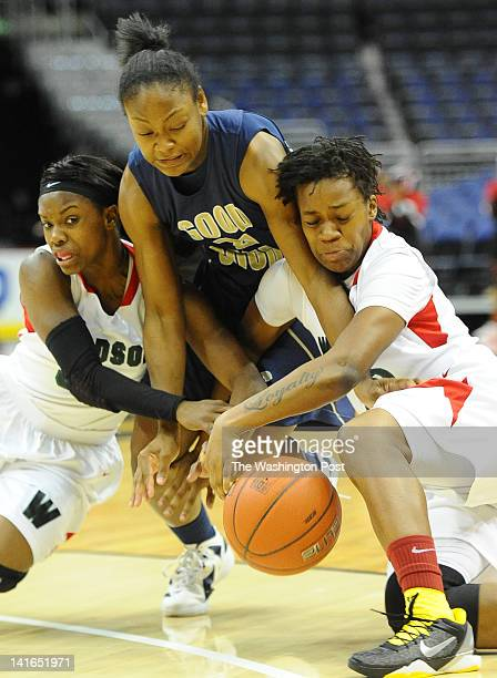 Good Counsel G Faith Randolph center fight for control of the ball against HD Woodson defenders Chanel Green and Janea Blount during 1st half action...