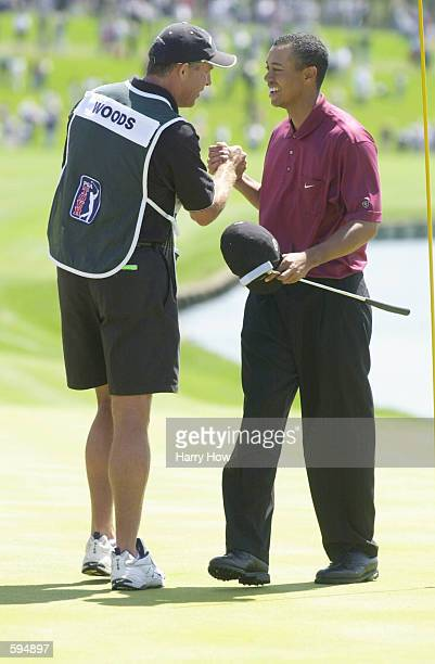 Tiger Woods is congratulated by his caddie Steve Williams at the TPC at Sawgrass after Woods won The Players Championship in Ponte Vedra Beach...