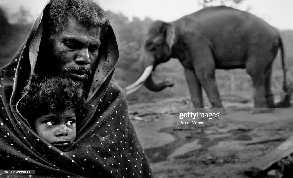 India, Top Slip, Father and daughter (4-5) wrapped in blanket, elephant in background : News Photo