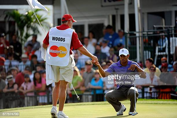 Tiger Woods and his caddie on the seventeenth green during the third round of the Arnold Palmer Invitational at the Bay Hill Club and Lodge's...
