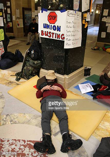 A protestor remaining inside the capitol rotunda rests in a protest of Wisconsin Governor Scott Walker's budget repair bill in Madison Wisconsin