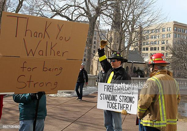 Madison fire fighter Tom Frederick gestures to show a Scott Walker supporter that money needs to come from the top on down outside the capitol...