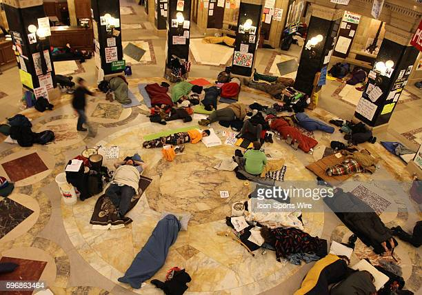 Protestors begin to wake up after sleeping inside the state capitol rotunda to protest Wisconsin Governor Scott Walker's budget repair bill in...