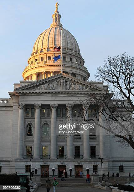 The Wisconsin State Capitol dome reflects the last light of the day as thousands continue to protest for the third week Wisconsin Governor Scott...