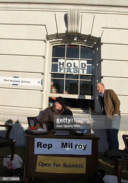 Wisconsin State Assembly man Nick Milroy sits at his outdoor office as Fred Clark talks with someone in Milroy's office with several Democrats moving...