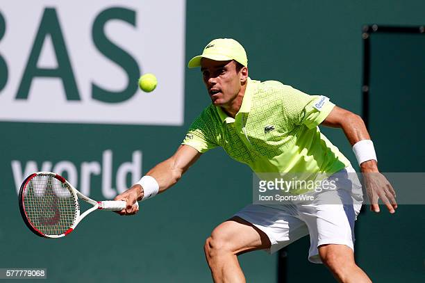 Roberto Bautista Agut of Spain returns a shot against Tomas Berdych of the Czech Republic during the BNP Paribas Open at Indian Wells Tennis Garden...