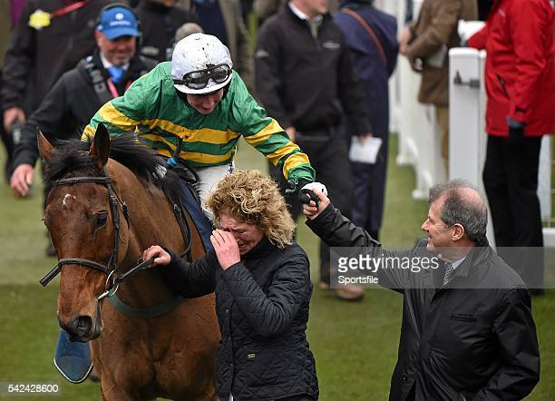 13 March 2015 Groom Sarah Bermingham leads in On The Fringe as jockey Nina Carberry is congratulated by owner JP McManus after winning the Foxhunter...