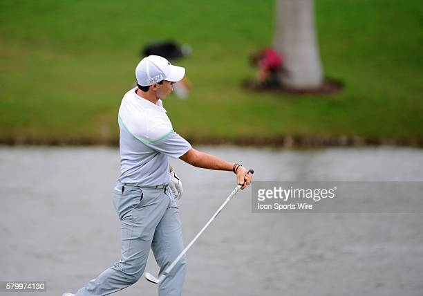 Rory McIlroy of Northern Ireland pretends to throw his club into the water on the 18th green after a fan asked him if that was his 3 iron during the...