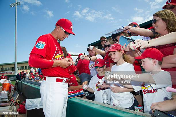 St Louis Cardinals Outfielder Stephen Piscotty signs autographs for fans in the stands before an MLB spring training game in which the Miami Marlins...