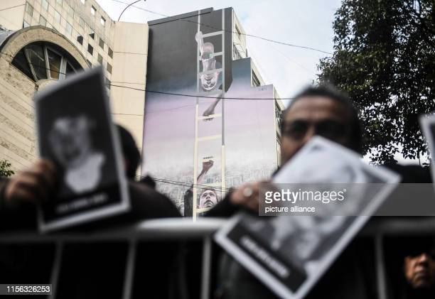 People hold up pictures of victims at a commemoration ceremony 25 years after the terrorist attack on the Jewish community AMIA in Buenos Aires In...