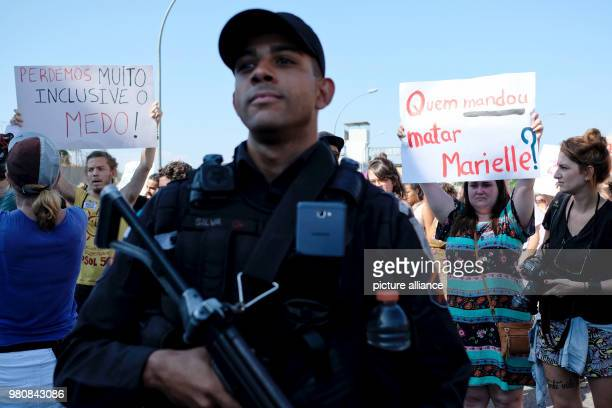 A police officer at the demonstration agaisnt the murder of politician and critic of police violence Marielle Franco He is standing in front of a...