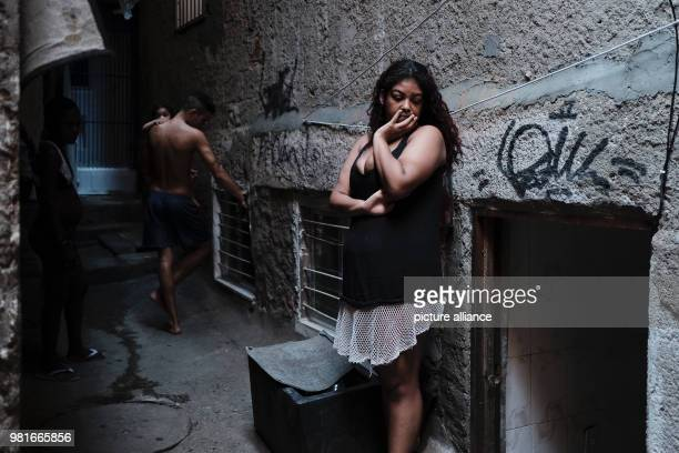 A woman lowers her face whilst she waits for help to repair a wall in her house in the favela Rochina Photo Diego Herculano/dpa