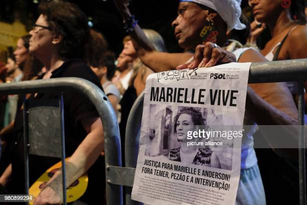 'Marielle is alive' stands on a small poster of a protestor during a rally after the murder of the Brazilian politician and critic of police violence...