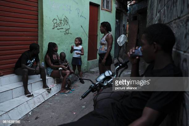 A girl speaking with a woman on a street in the Rocinha favela Photo Diego Herculano/dpa