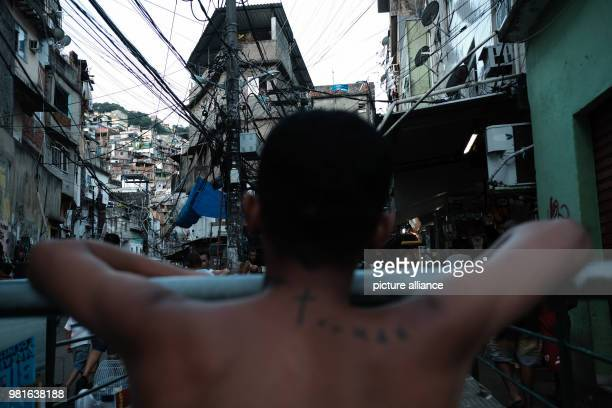 A man looking at a sky filled with cables in the Rocinha favela Photo Diego Herculano/dpa