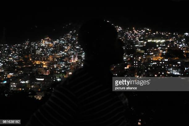 A man walking through the night while the Rocinha favela shines in the background Photo Diego Herculano/dpa