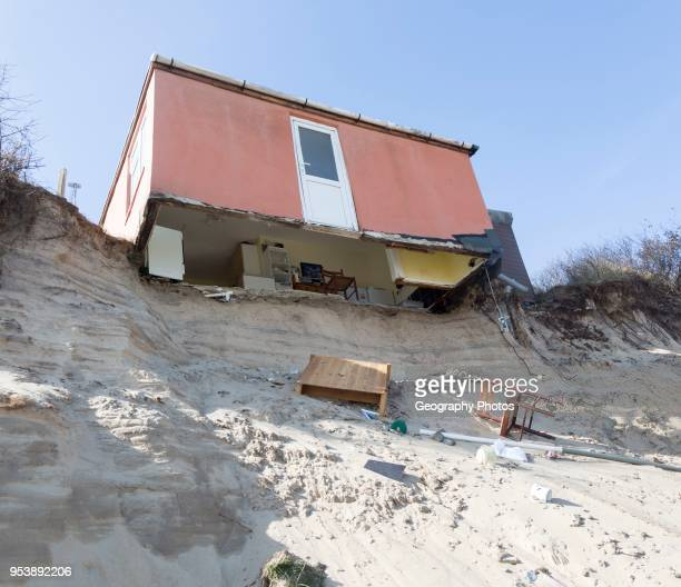 March 2018 Clifftop property collapsing due to coastal erosion after recent storm force winds Hemsby Norfolk England UK