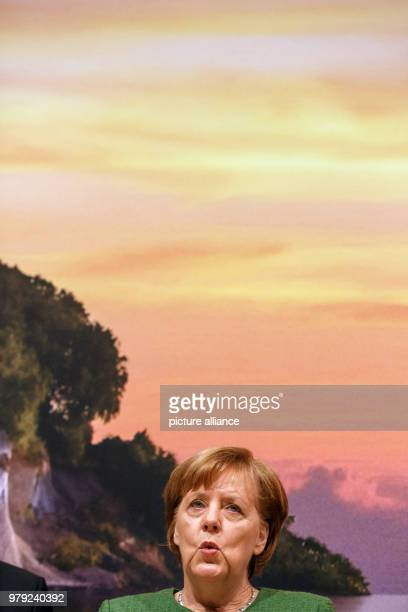March 2018, Germany, Berlin: German Chancellor Angela Merkel sings during her visit to the fair stand of the federal state Mecklenburg-Western...
