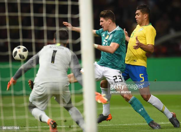 27 March 2018 Germany Berlin Olympia Stadium Soccer Friendly International matchGermany vs Brazil Brazil's goalkeeper Alisson Germany's Mario Gomez...