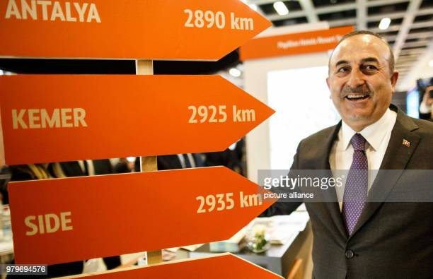 March 2018, Germany, Berlin: Turkish Minister of Foreign Affairs Mevlut Cavusoglu stands next to signs leading to Antalya, Kemer and Side at the...