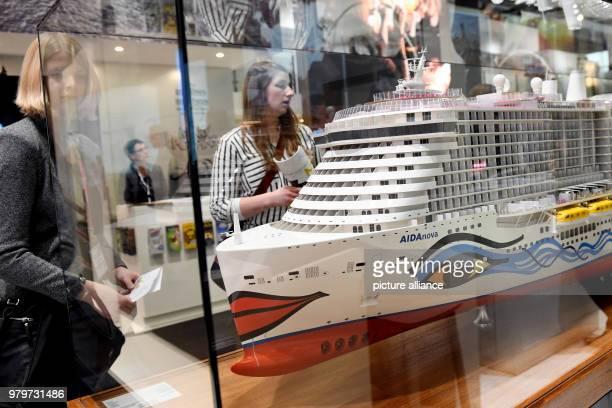 Visitors looking at a model of a Aida cruise ship at the International Tourism Fair Photo Maurizio Gambarini/dpa