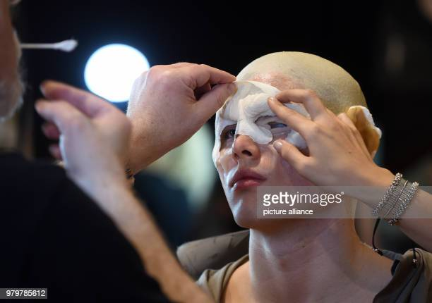 A makeup artist fits a latex mask on a model at the talk forum of the trade fair 'makeup artist design show' Photo Horst Ossinger/dpa