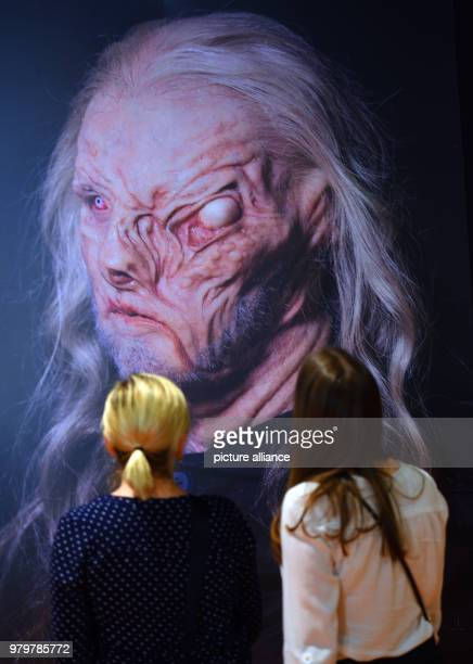 Two women take a look at a photograph depicting a horror mask at the talk forum of the trade fair 'makeup artist design show' Photo Horst Ossinger/dpa