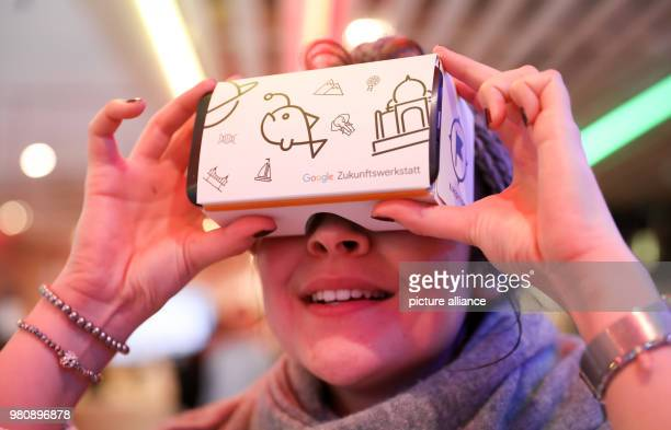 A young woman looking into a pair of Google virtual reality glasses before a press conference for the Google future workshop Hamburg Teachers and...