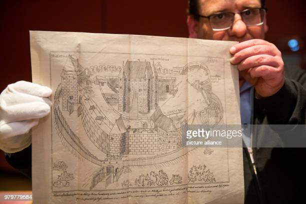 Markus Mergenthaler director of the KnaufMuseum Iphofen holds up a woodblock print from the year 1554 The print shows the conquered stronghold of...