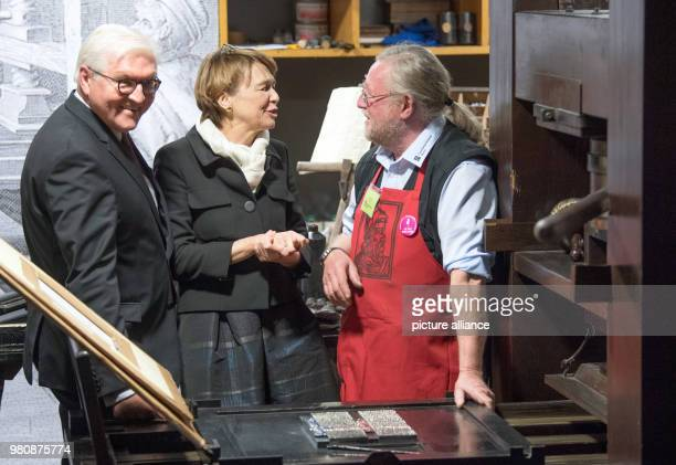 A printer explains a printing press to the German President FrankWalter Steinmeier and his wife Elke Buedenbender during their visit to the Gutenberg...