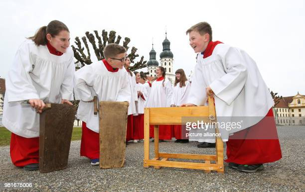 Outside the St Peter and Paul cathedral Catholic ministrants turn a traditional wooden instrument whose sound will replace the church bells over...