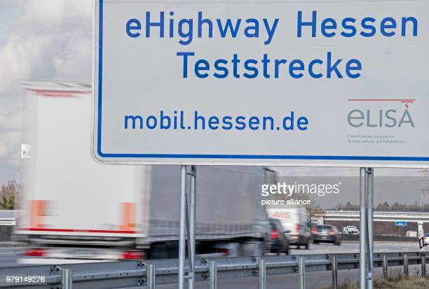 Two lorries drive past a sign marking the beginning of a test track for 'eHighway Hessen' Over a stretch of 5km electric lorries will be supplied...