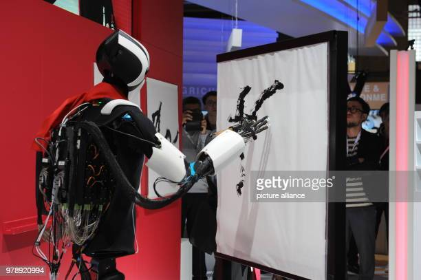 A robot from the Japanese Telekom company Docomo paints a picture at the Mobile World Congress 2018 by copying the movements of a human which are...