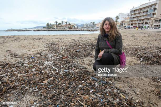 Resident Aina Barcelò crouching on the beach where rubbish mixed with sanitary products is mixed with Neptune grass Sewage works in Palma quickly...