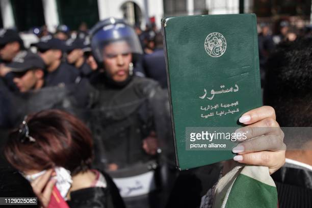 A protester holds up a copy of the Algerian constitution during a demonstration organized by Algerian lawyers outside the Constitutional Council to...