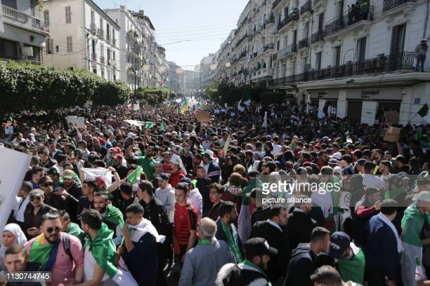 People march during a protest against President Abdelaziz Bouteflika's decision to withdraw from and postpone the presidential elections of April...